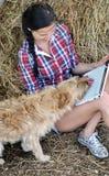 Νέα ελκυστική γυναίκα που χρησιμοποιεί το φορητό προσωπικό υπολογιστή με το σκυλί Στοκ εικόνα με δικαίωμα ελεύθερης χρήσης