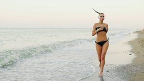 Νέα ελκυστική γυναίκα στο μαύρο μαγιό δέρματος που τρέχει θαλασσίως στην παραλία Το ponytail της κυματίζει στον αέρα απόθεμα βίντεο