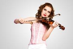 Νέα ελκυστική γυναίκα στο ρόδινο κορσέ σε ένα βιολί Στοκ Εικόνα