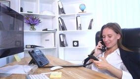 Νέα ελκυστική επιχειρηματίας που μιλά στο τηλέφωνο και τη χρησιμοποίηση του smartphone στο γραφείο και το χαμόγελο Στοκ φωτογραφίες με δικαίωμα ελεύθερης χρήσης
