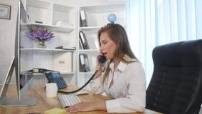 Νέα ελκυστική επιχειρηματίας που μιλά στο τηλέφωνο στο γραφείο και το χαμόγελο Στοκ εικόνα με δικαίωμα ελεύθερης χρήσης