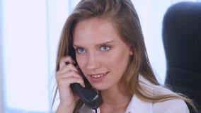 Νέα ελκυστική επιχειρηματίας που μιλά στο τηλέφωνο στο γραφείο και το χαμόγελο κλείστε επάνω Στοκ Φωτογραφία