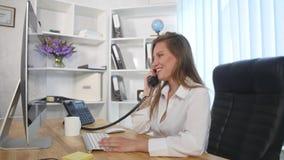 Νέα ελκυστική επιχειρηματίας που μιλά στο τηλέφωνο στο γραφείο και το χαμόγελο Στοκ εικόνες με δικαίωμα ελεύθερης χρήσης