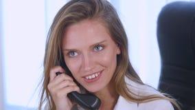 Νέα ελκυστική επιχειρηματίας που μιλά στο τηλέφωνο στο γραφείο και το χαμόγελο κλείστε επάνω Στοκ Φωτογραφίες
