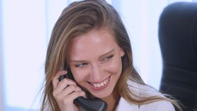 Νέα ελκυστική επιχειρηματίας που μιλά στο τηλέφωνο στο γραφείο και το χαμόγελο κλείστε επάνω Στοκ εικόνα με δικαίωμα ελεύθερης χρήσης