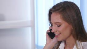 Νέα ελκυστική επιχειρηματίας που μιλά στο τηλέφωνο στο γραφείο Στοκ Φωτογραφία