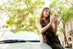Επιχειρηματίας που κλίνει στο αυτοκίνητο με το smartphone. Στοκ Εικόνες