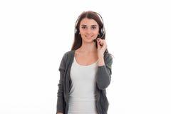 Νέα ελκυστική επιχειρησιακή κυρία με το ακουστικό και μικρόφωνο στην ομοιόμορφη εξέταση τη κάμερα και το χαμόγελο που απομονώνετα Στοκ εικόνα με δικαίωμα ελεύθερης χρήσης