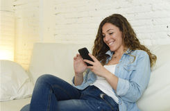 Νέα ελκυστική ισπανική γυναίκα χρησιμοποιώντας το κινητό τηλέφωνο app ή texting στον εγχώριο καναπέ Στοκ Φωτογραφίες