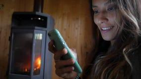 Νέα ελκυστική μικτή γυναίκα φυλών που χαμογελά και που χρησιμοποιεί το κινητό τηλέφωνο κοντά στην εστία Άνετος και τεχνολογία HD  απόθεμα βίντεο