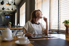 Νέα ελκυστική συνεδρίαση γυναικών με την ψηφιακά ταμπλέτα και τα ακουστικά στο σύγχρονο καφέ Στοκ Εικόνα