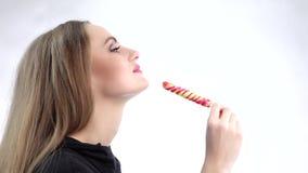 Νέα ελκυστική όμορφη συγκινημένη γυναίκα που τρώει το ζωηρόχρωμο lollipop κίνηση αργή φιλμ μικρού μήκους