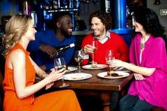 Νέα ζεύγη που απολαμβάνουν το γεύμα τους με τα ποτά Στοκ εικόνα με δικαίωμα ελεύθερης χρήσης