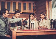 Νέα ζεύγη που πίνουν το καυτό τσάι στο χειμερινό εξοχικό σπίτι Στοκ Εικόνες