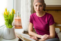 Νέα θετική ενήλικη θηλυκή συνεδρίαση ασθενών με καρκίνο στην κουζίνα από ένα παράθυρο που διαβάζει ένα βιβλίο, χαμόγελο στοκ εικόνες