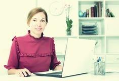 Νέα θετική θηλυκή δακτυλογράφηση υπαλλήλων στο φορητό υπολογιστή Στοκ φωτογραφία με δικαίωμα ελεύθερης χρήσης