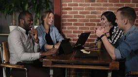 Νέα θετική ομάδα τεσσάρων μικτών συναγωνισμένων ανθρώπων που χρησιμοποιούν τα lap-top ταμπλέτες και smartphones συνεδρίαση στον ε απόθεμα βίντεο