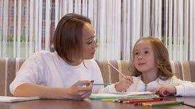 Νέα θετική χαριτωμένη μητέρα που κάνει το σχέδιο με την λίγη όμορφη κόρη απόθεμα βίντεο