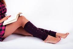 Νέα θηλυκά πόδια με τα μαγκάές και βιβλίο εκμετάλλευσης κοριτσιών στα γόνατα στοκ εικόνες
