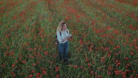 Νέα θηλυκή γυναίκα blogger στον τομέα λουλουδιών απόθεμα βίντεο