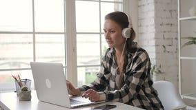 Νέα θηλυκή μουσική ακούσματος σχεδιαστών ιδιοκτητών επιχείρησης στα ακουστικά εργαζόμενων στο lap-top πωλήτρια φιλμ μικρού μήκους