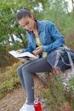 Νέα θηλυκή οδοιπορία οδοιπόρων στη φύση και έρευνα των κατευθύνσεων στοκ εικόνα με δικαίωμα ελεύθερης χρήσης