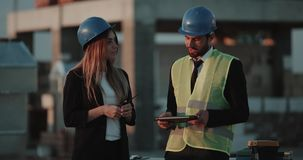 Νέα θηλυκό και άτομο συνεργατών δύο που κάνουν στη διαπραγμάτευση στο εργοτάξιο οικοδομής, αυτοί που φορούν τον εξοπλισμό ασφάλει απόθεμα βίντεο