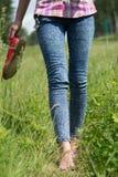 Νέα θηλυκά πόδια που περπατούν στη χλόη το καλοκαίρι Στοκ Εικόνα
