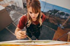 Νέα θηλυκή εικόνα ζωγραφικής καλλιτεχνών στο στούντιο Στοκ Φωτογραφία
