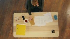 Νέα θηλυκή επιχειρηματίας που χρησιμοποιεί το τηλέφωνο κυττάρων στο γραφείο, που έχει το τηλεφώνημα απόθεμα βίντεο