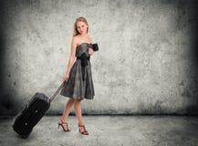 Νέα θηλυκή στάση με την τσάντα ταξιδιού της στοκ φωτογραφία