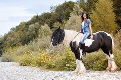 Νέα θηλυκή συνεδρίαση στο άλογό της και εξέταση το γ Στοκ Εικόνα