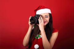 Νέα θηλυκή φωτογραφία που κάνει τη φωτογραφία στο κόκκινο holdi υποβάθρου Στοκ Φωτογραφία