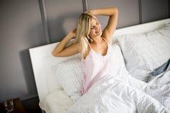 Νέα διάθεση κοριτσιών ομορφιάς ξυπνήστε το πρωί στο κρεβάτι της στο σπίτι Στοκ Εικόνα