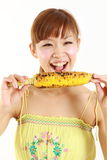 Νέα ιαπωνική γυναίκα με το ψημένο στη σχάρα καλαμπόκι Στοκ Εικόνες