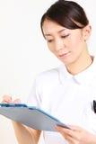 Νέα ιαπωνική νοσοκόμα με το κλινικό αρχείο Στοκ φωτογραφία με δικαίωμα ελεύθερης χρήσης