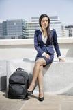 Νέα ινδική επιχειρηματίας με τη συνεδρίαση αποσκευών υπαίθρια στοκ εικόνες