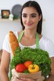 Νέα ισπανική γυναίκα σε ένα πράσινο μαγείρεμα ποδιών στην κουζίνα Σύνολο τσαντών εγγράφου εκμετάλλευσης νοικοκυρών των λαχανικών  Στοκ φωτογραφία με δικαίωμα ελεύθερης χρήσης