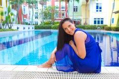 Νέα ισπανική γυναίκα στην μπλε χαλάρωση φορεμάτων από την πισίνα που περιβάλλεται από τα λουλούδια Στοκ εικόνα με δικαίωμα ελεύθερης χρήσης