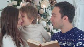 Νέα ιστορία Χριστουγέννων ανάγνωσης πατέρων, ενώ μητέρα και ο ευτυχής γιος τους που ψιθυρίζουν κρυφά στοκ φωτογραφία με δικαίωμα ελεύθερης χρήσης