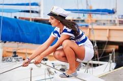 Νέα ισχυρή γυναίκα που πλέει τη βάρκα, ύφος θάλασσας στο λιμένα στοκ εικόνες