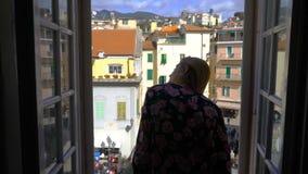 Νέα ιταλική μεσαιωνική πόλη πρωινού παραθύρων ανοίγματος γυναικών φιλμ μικρού μήκους
