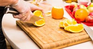 Νέα καθαρά χέρια αρχιμαγείρων που κόβουν το πορτοκάλι στον πίνακα Στοκ εικόνες με δικαίωμα ελεύθερης χρήσης