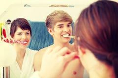 Νέα καθαρίζοντας δόντια ζευγών Στοκ φωτογραφία με δικαίωμα ελεύθερης χρήσης