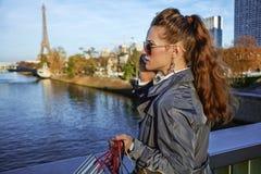 Νέα καθιερώνουσα τη μόδα γυναίκα που μιλά στο τηλέφωνο κυττάρων κοντά στον πύργο του Άιφελ Στοκ Φωτογραφίες
