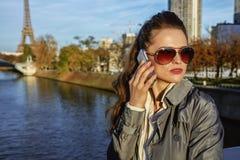 Νέα καθιερώνουσα τη μόδα γυναίκα που μιλά στο τηλέφωνο κυττάρων κοντά στον πύργο του Άιφελ Στοκ Φωτογραφία