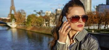 Νέα καθιερώνουσα τη μόδα γυναίκα που μιλά στο τηλέφωνο κυττάρων κοντά στον πύργο του Άιφελ Στοκ Εικόνες