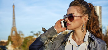 Νέα καθιερώνουσα τη μόδα γυναίκα που μιλά στο smartphone κοντά στον πύργο του Άιφελ Στοκ Φωτογραφίες