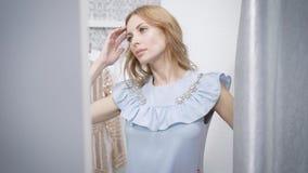 Νέα και αρκετά ξανθά βλέμματα στον καθρέφτη, μια κυρία που ντύνεται σε ένα βεστιάριο ένα νέο φόρεμα θέλει να αγοράσει απόθεμα βίντεο