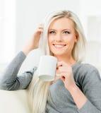 Νέα και ευτυχής γυναίκα που στηρίζεται στον καναπέ στο σπίτι και τον καφέ κατανάλωσης Στοκ Εικόνες